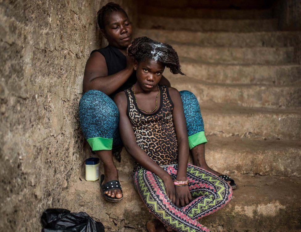 A mother washes her daughter's hair on the steps of the house