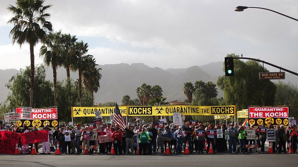 Protesters hold signs that say 'quarantine the kochs''