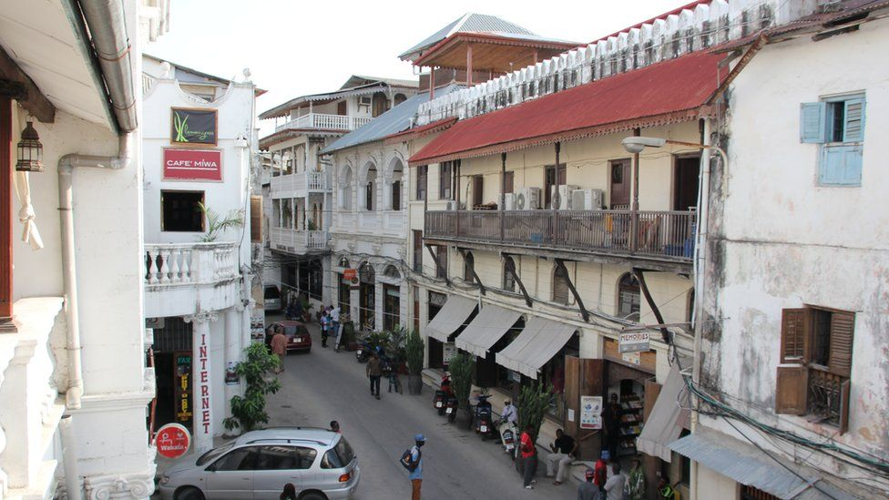 People walk in the street close to Freddie Mercury House in Stone Town, the historic part of Zanzibar City