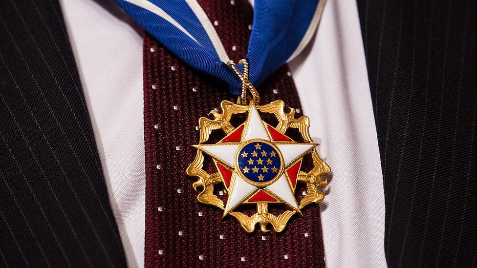 US Presidential medal of freedom hanging over a red tie