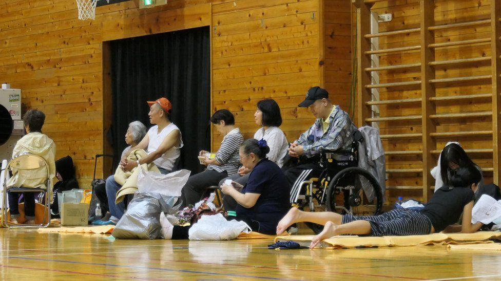 Evacuated residents sit inside a shelter to wait out the storm in Tokyo on 12 October 2019.