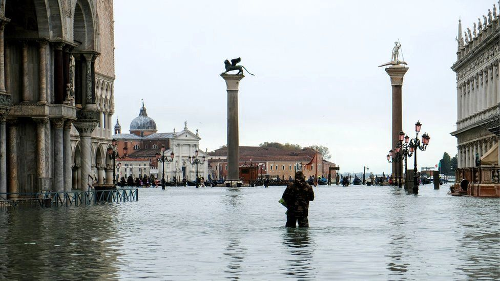 A man stands in water at the flooded St Mark's Square during exceptionally high water levels in Venice, Italy, 13 November 2019