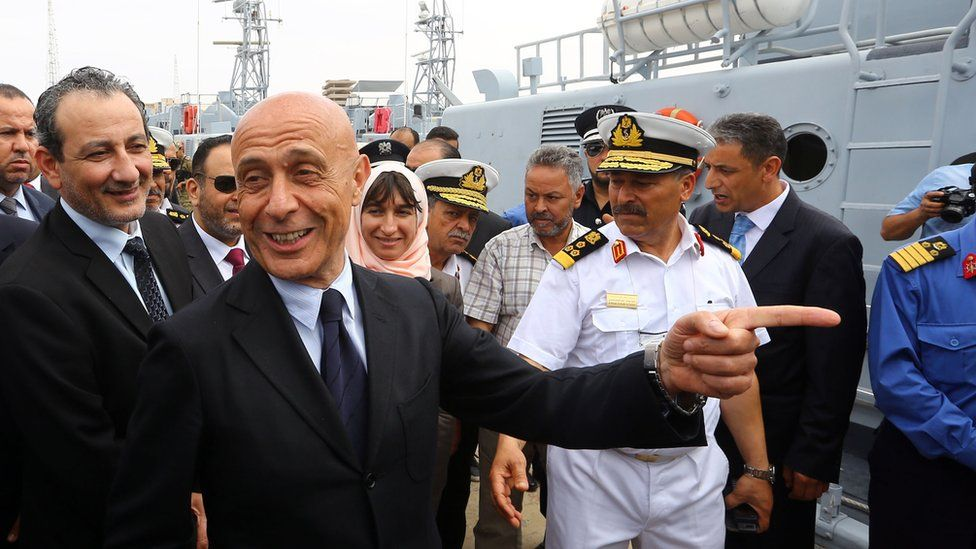 Marco Minniti laughs alongside Libyan Defence Minister (of the UN-backed government) at the harbour next to some Libyan coast guard vessels, while naval personnel can also be seen nearby