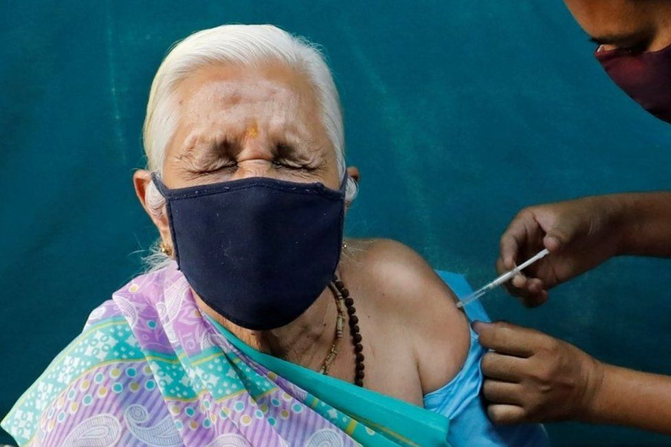 A woman reacts as she receives a dose of COVISHIELD, a coronavirus disease (COVID-19) vaccine manufactured by Serum Institute of India, at a vaccination centre in Ahmedabad, India, March 27,
