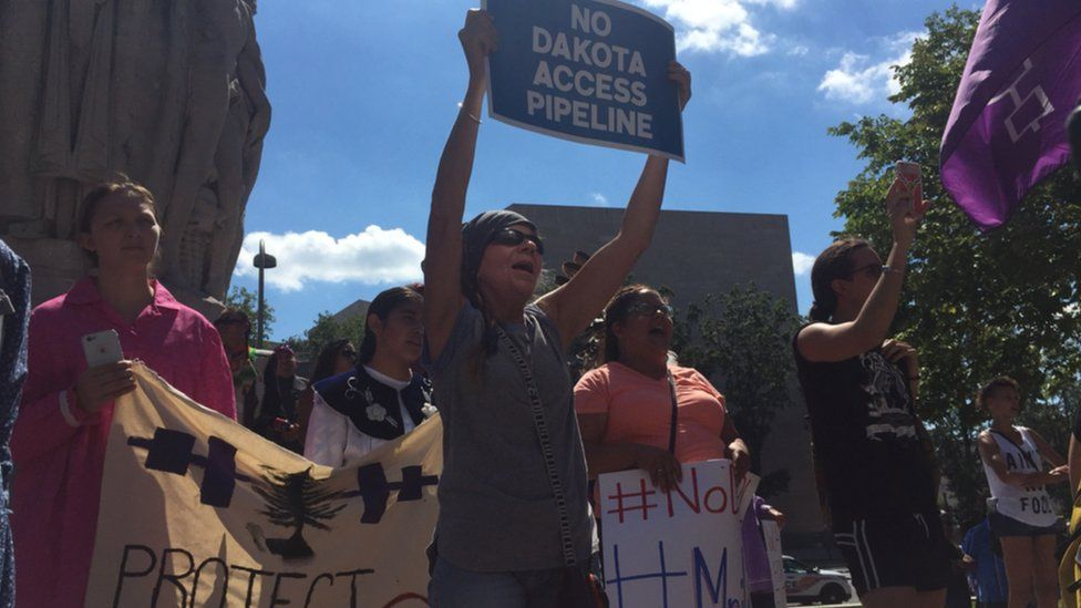 Protesters outside the US District Court in Washington cheer as members of Native American community rally against the construction of the Dakota Access pipeline.