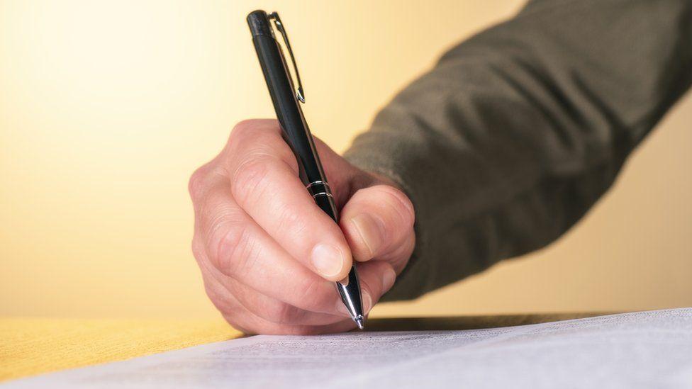A man handwriting a letter