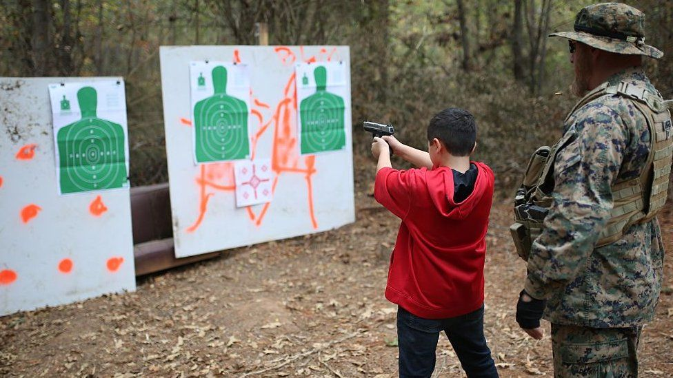 11-years-old Ashton (L), son of the former marine and the leader of the Georgia Security Forces (GSF) Chris Hill also known as General Bloodagent, takes part in a real gun target practice with the guidance of his father during a military drill in a forest with other group members in Flovilla, Georgia, USA on November 12, 2016.