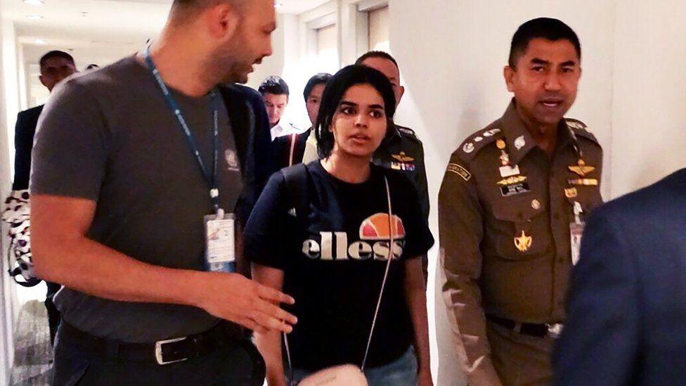 Saudi woman Rahaf Mohammed al-Qunun is escorted by Thai immigration and UN officials at Bangkok's Suvarnabhumi international airport in Bangkok