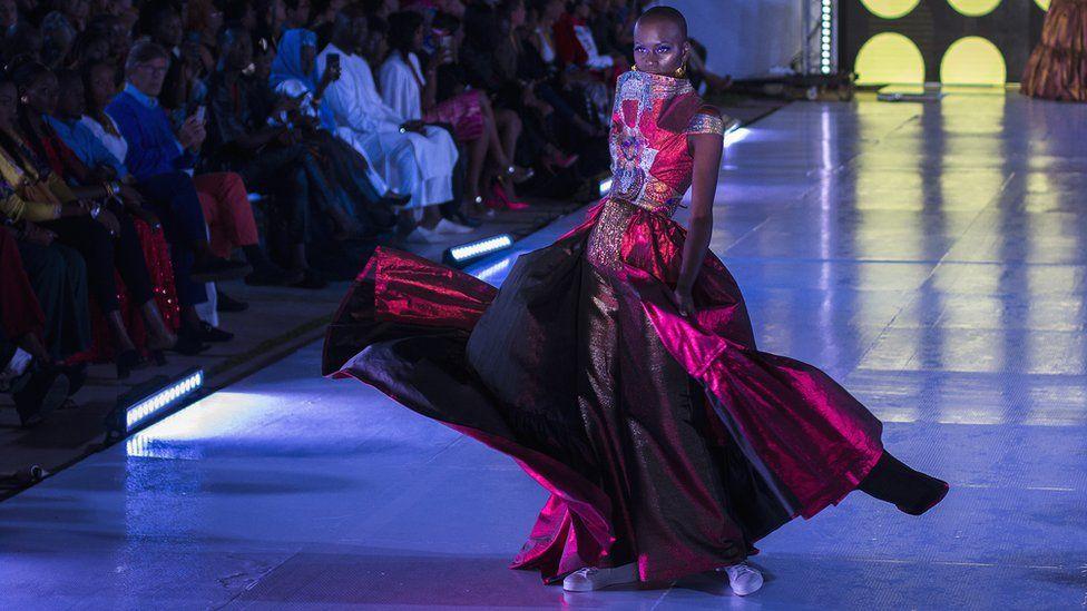 La mannequin sénégalaise Alima Diop pose sur le podium en portant un dessin d'Algaye lors de la Semaine de la mode de Dakar à Dakar, Sénégal.