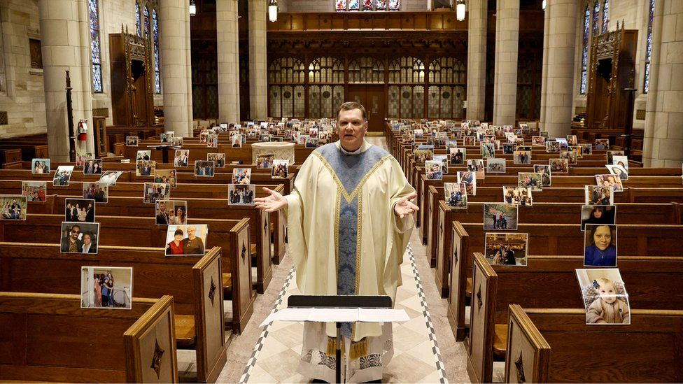 Rev Brian X Needles live-streams Easter Sunday Mass to picture print-outs sent in by parishioners and attached to pews by staff at Our Lady of Sorrows Catholic Church in South Orange, New Jersey, 12 April 2020