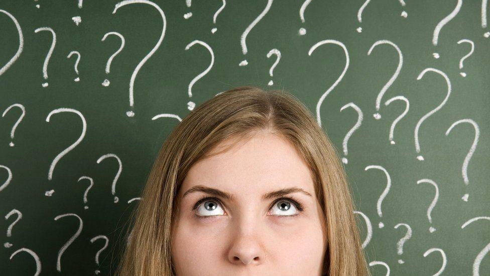 Thinking woman in front of question marks written blackboard