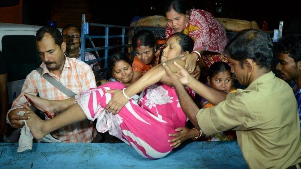 Indian rescuers help an earthquake victim in Siliguri, West Bengal (13 April 2016)
