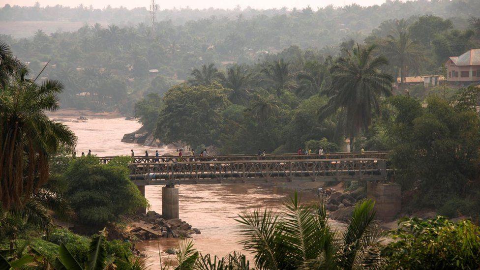 Pessoas caminham na ponte que passa sobre o rio Kasai