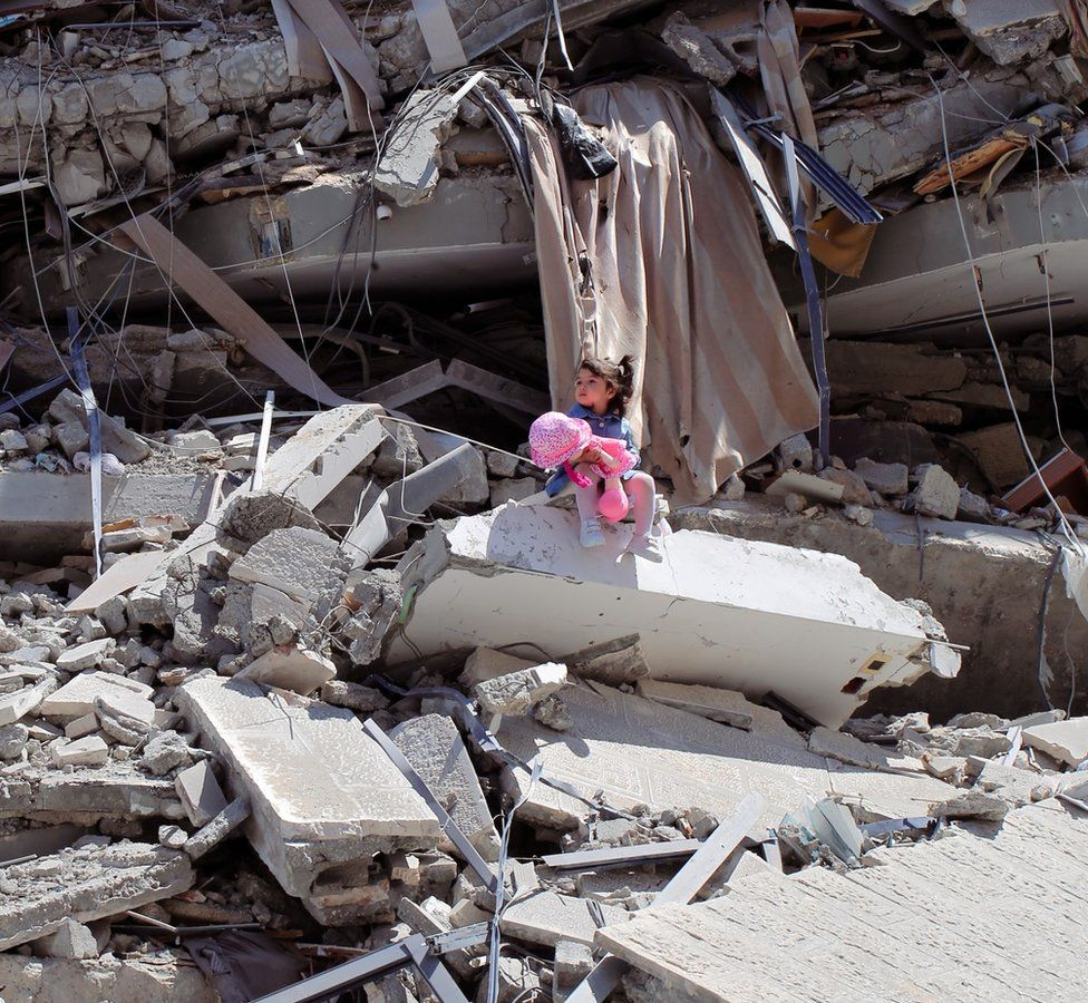 Celine by Shaban El Sousi - a photo showing a two-year-old Palestinian girl sitting on the ruins of a tower block in Gaza in May 2021