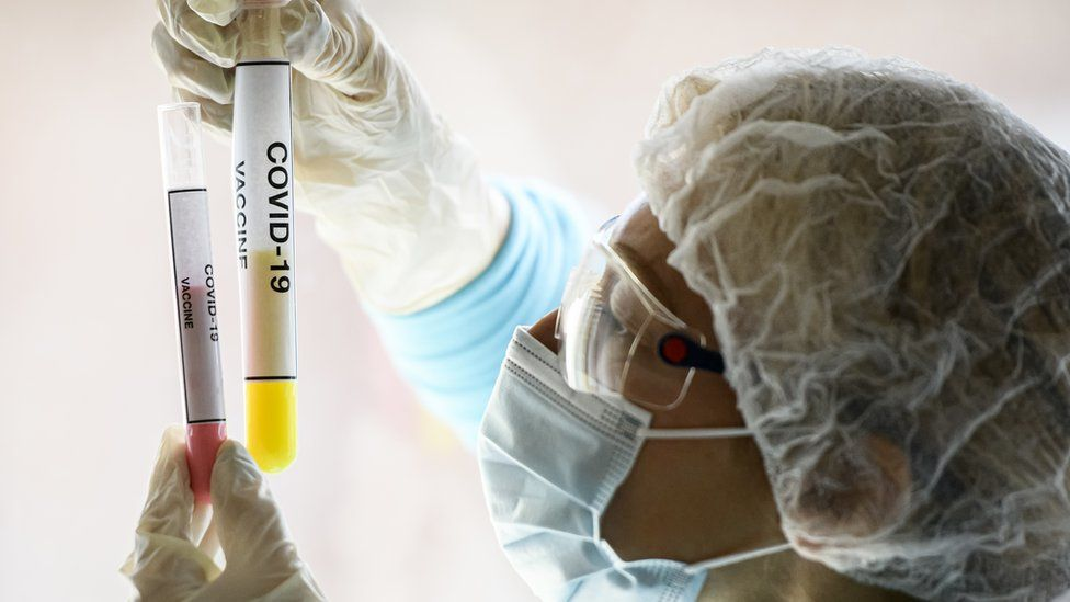 A woman in a mask holds up test tubes with Covid-19 vaccine written on them
