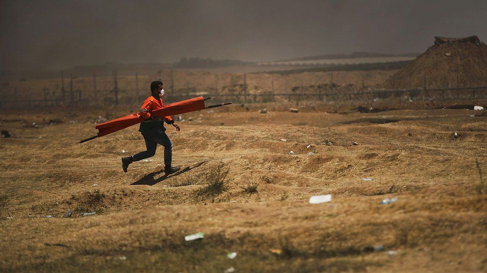 A lone medic runs to a person who was shot along the border fence with Israel as mass demonstrations continue