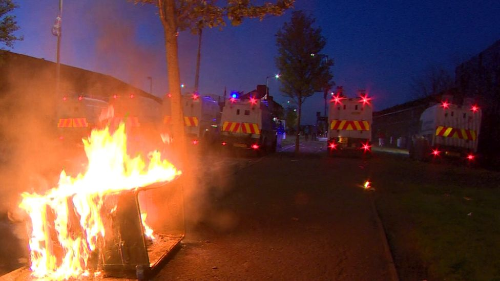 Police Land Rovers parked near a burning bin in Belfast