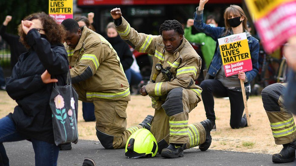 A firefighter in uniform kneels during the protest