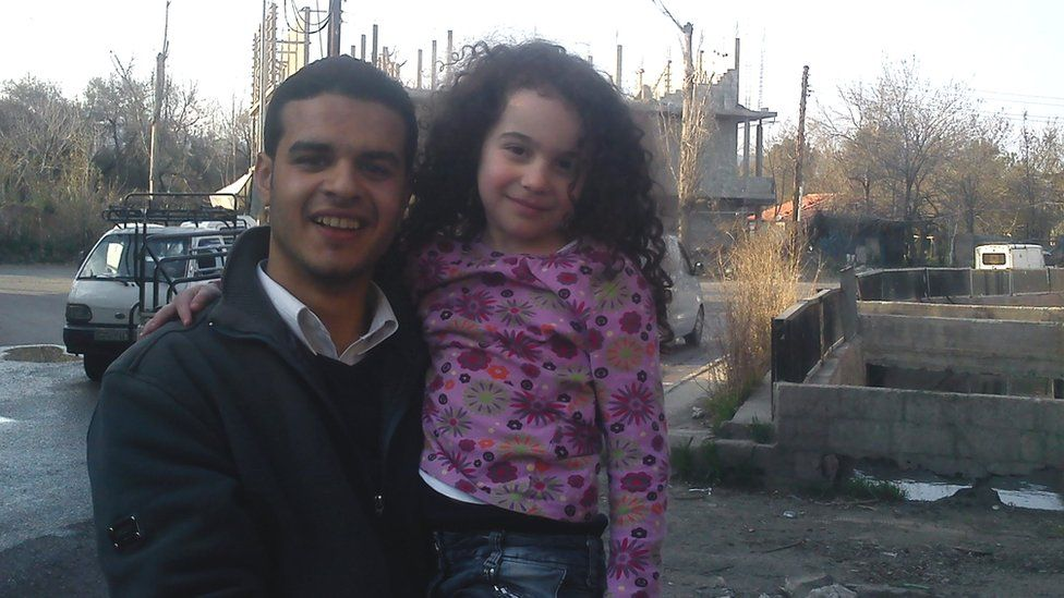 Mouaz al-Balkhi holding a little girl in pink shirt - when he was a first year university student and helped Syrians who fled from Homs to Damascus