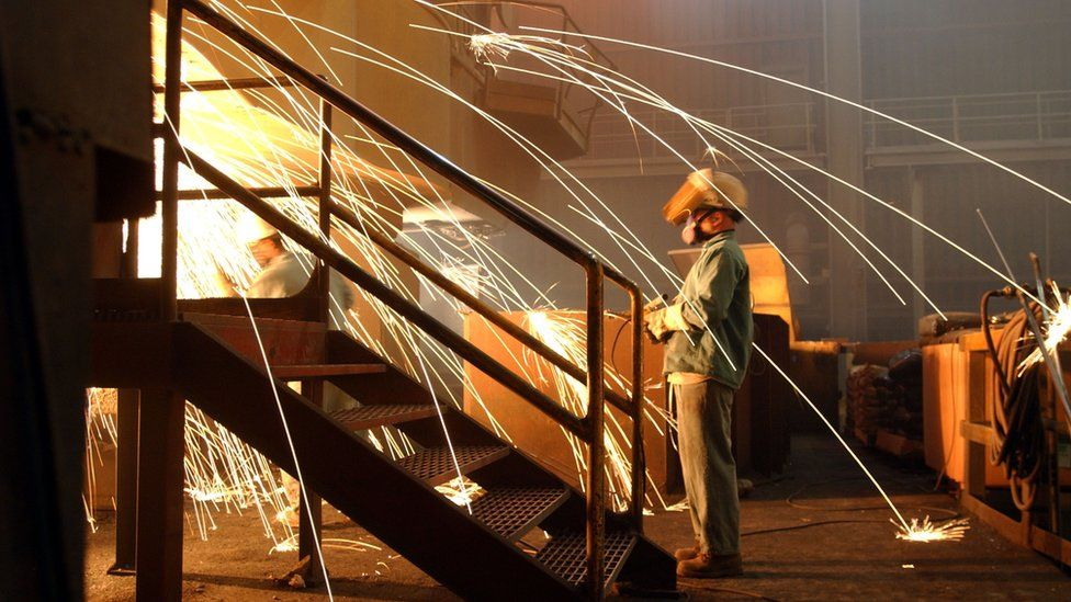 A worker wearing a respirator keeps an eye on molten steel at the TAMCO steel mini mill