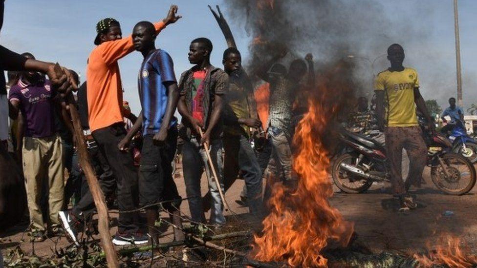 Demonstrators shout slogans next to burning tyres in Ouagadougou. Photo: 21 September 2015