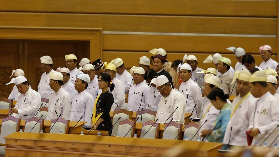 Aung San Suu Kyi surrounded by other politicians at a parliamentary session