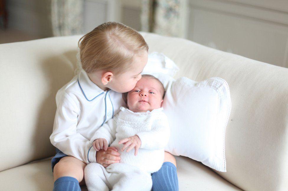 Prince George holding baby Princess Charlotte