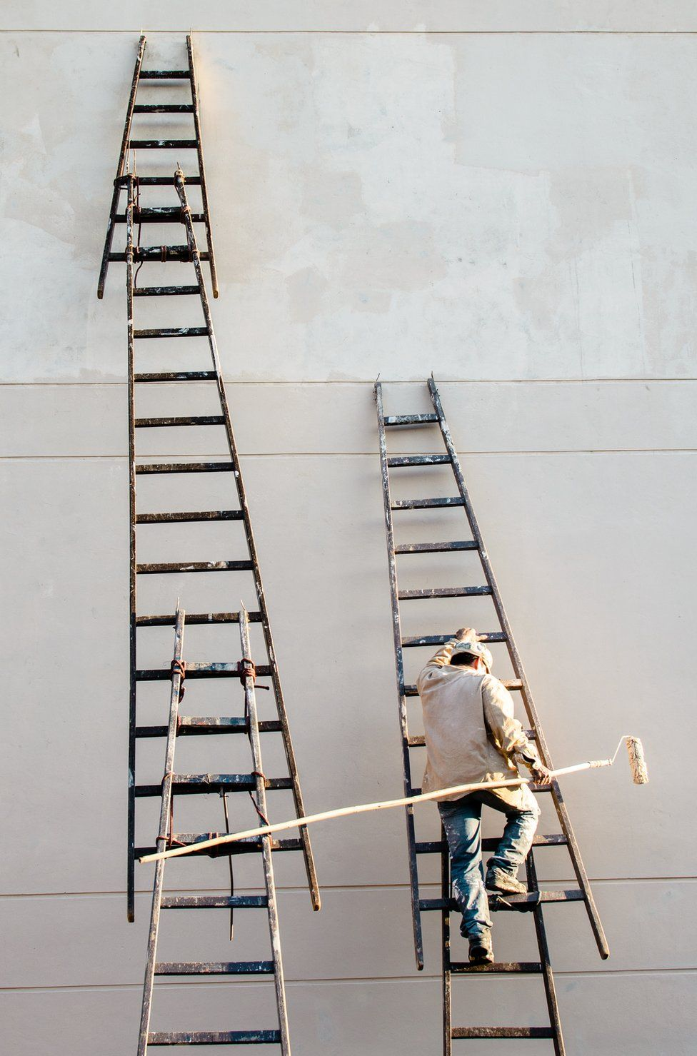 A man climbs roughly tied together ladders