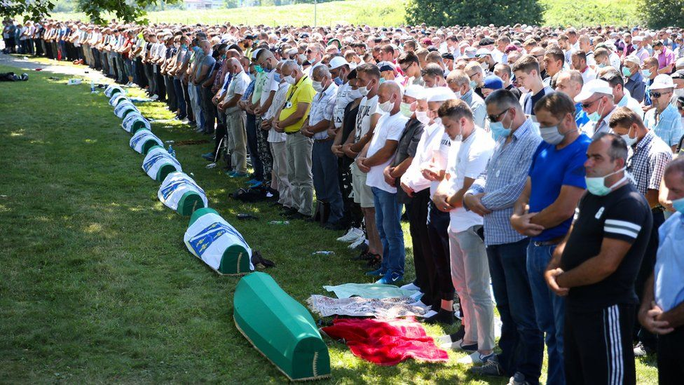 People praying at a memorial event