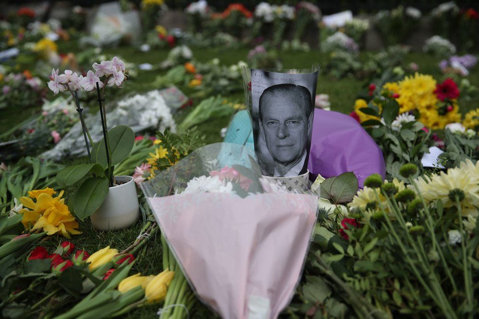 People leave flowers outside Windsor Castle, Berkshire, following the death of the Duke of Edinburgh