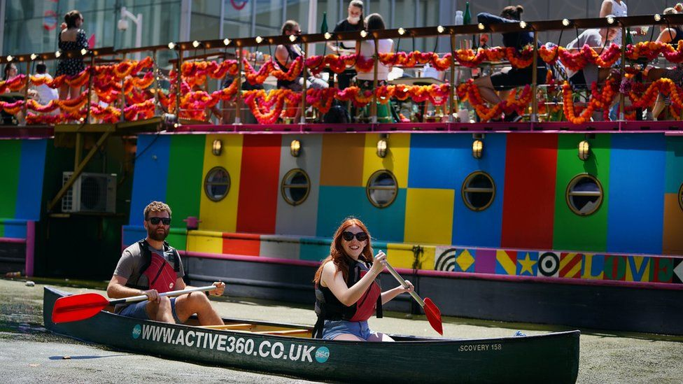 A couple enjoy the hot weather in a canoe on the canal in Paddington Basin, north London on Bank Holiday Monday