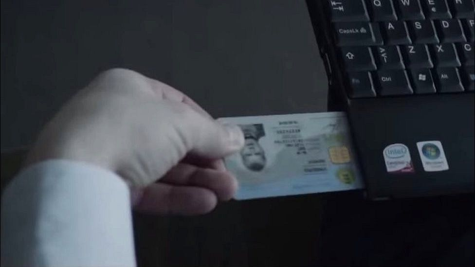 Man inserting digital ID card into laptop
