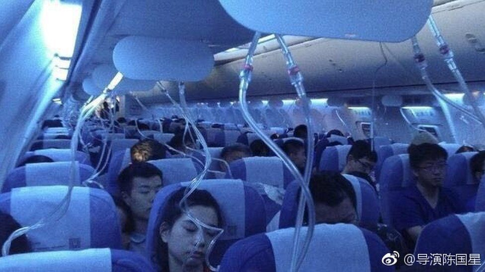 Aircraft passengers with oxygen masks dropped
