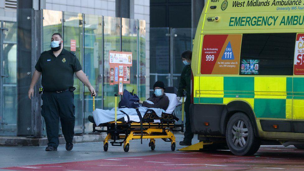 Health workers transport a patient outside the Queen Elizabeth Hospital Birmingham