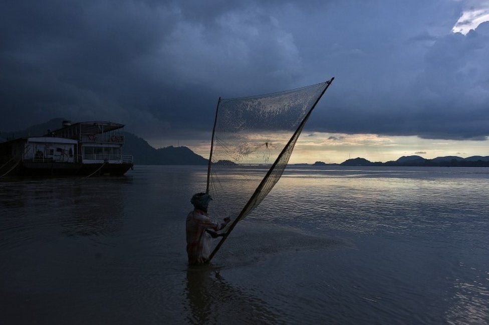 A man catches fish at the banks of the Brahmaputra river in Guwahati, India August 28, 2017