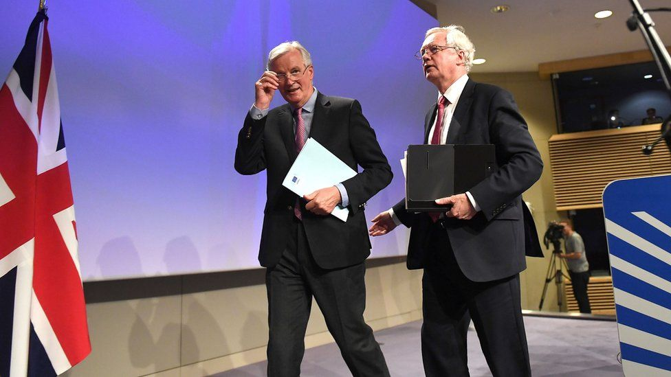 David Davis and Michel Barnier leave the stage after a press conference.