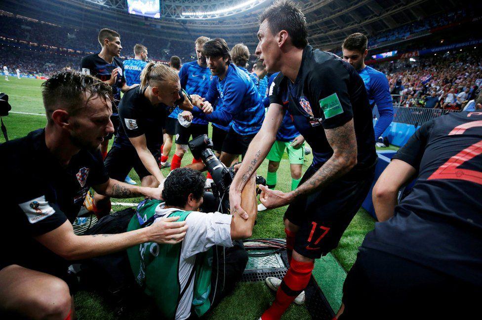 Croatia's Mario Mandzukic helps an AFP photographer Yuri Cortez to his feet after celebrating scoring their second goal