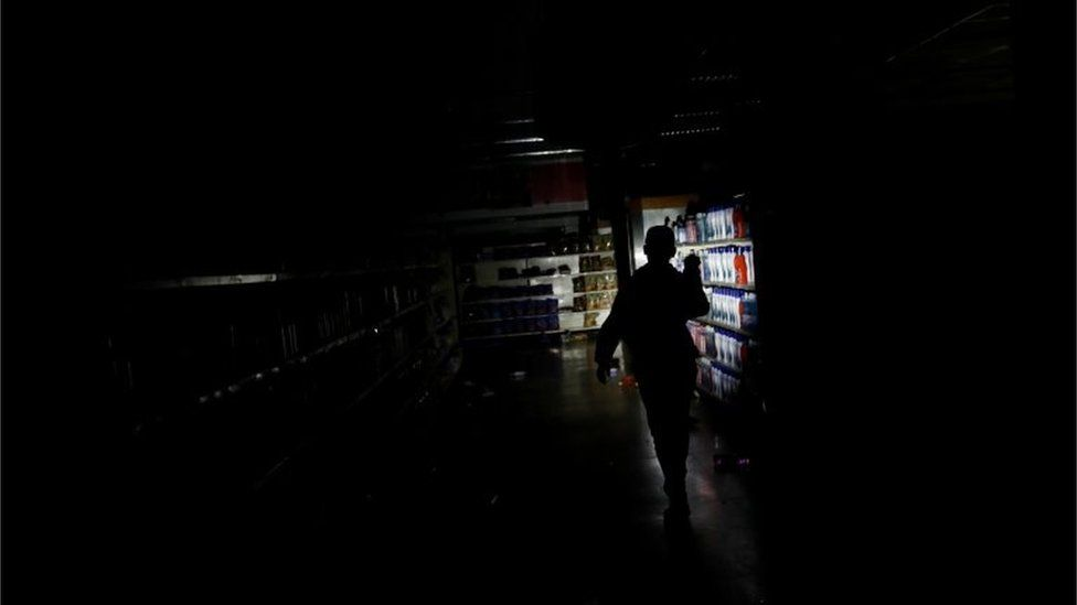 A worker inspects damage in a supermarket after it was looted during an ongoing blackout in Caracas, Venezuela March 10, 2019.