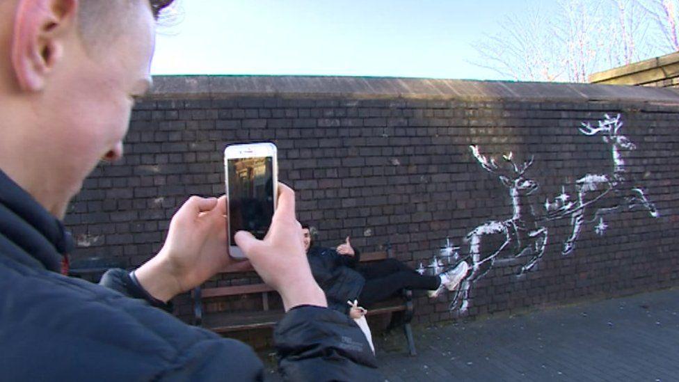 A visitor recreates the scene