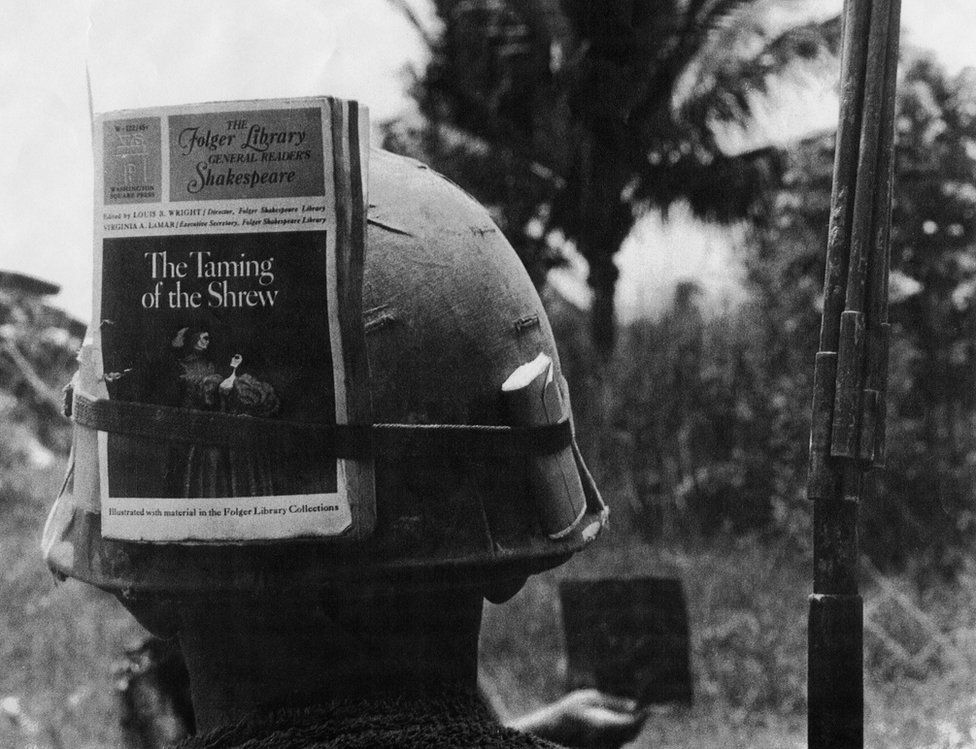 American soldier in Vietnam with a copy of the Folger Shakespeare edition of The Taming of the Shrew tied to his helmet