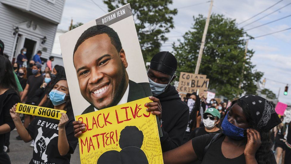A demonstrator holds a sign for Botham Jean while marching during a demonstration on June 9, 2020