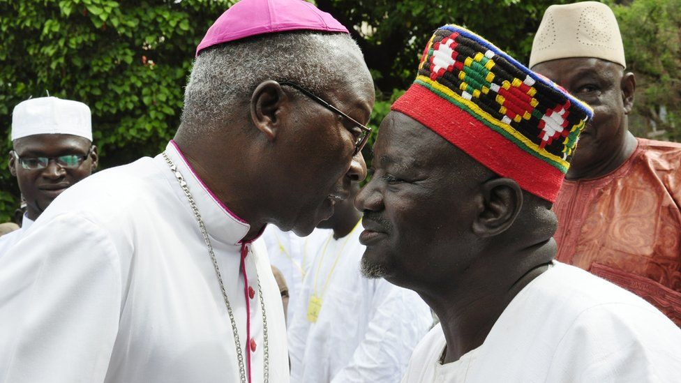 Archbishop of Ouagadougou Philippe Ouedrago (L) wishes a good Eid to Burkinabe chief the Mogho Naba Baongo in Burkina Faso, 2012