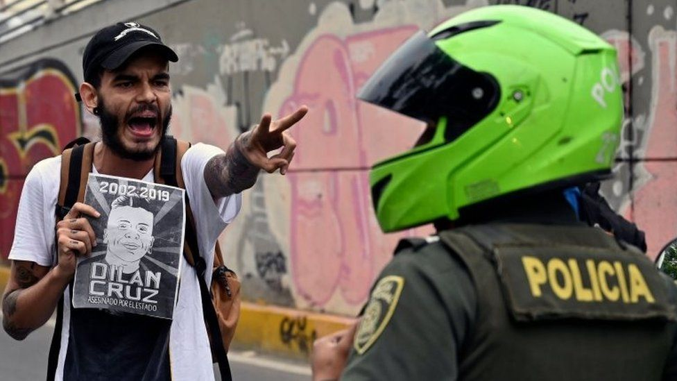 A demonstrator holding a poster of the late Dilan Cruz shouts at riot police during a march against the government of Colombian President Ivan Duque during a national strike in Cali on November 27, 2019