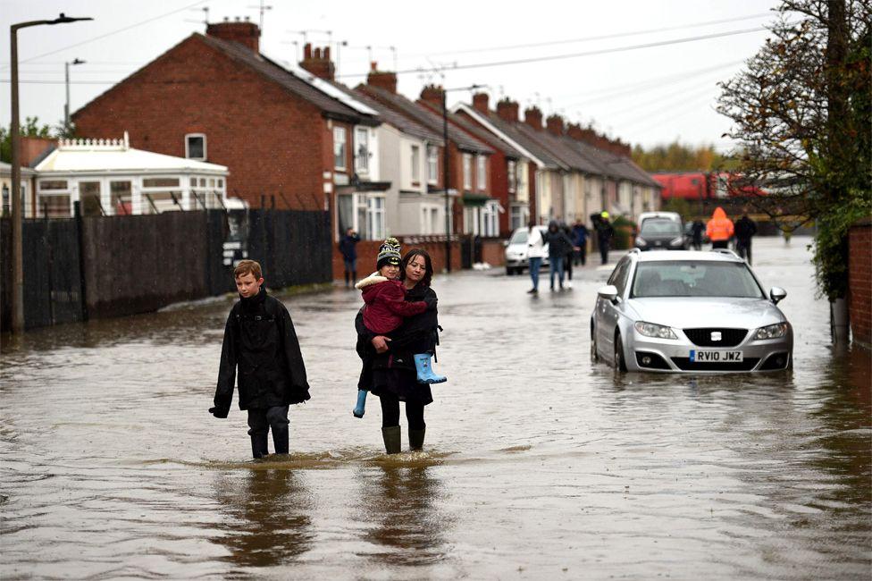 Banorët ecin nëpër ujërat e përmbytjes