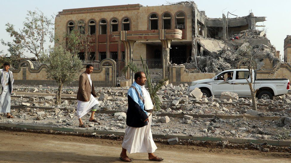 Yemenis walk past a building, housing branches of the Finance Ministry and Central Bank, that was heavily damaged in an airstrike by the Saudi-led coalition, in the northern province of Saada