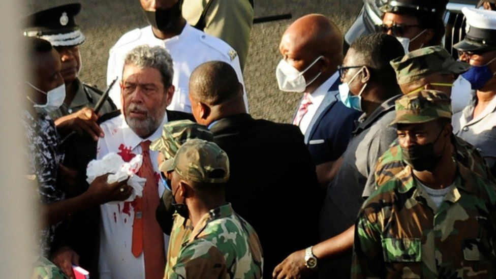 Ralph Gonsalves, his shirt covered in blood, is evacuated after being hit in the head by a stone