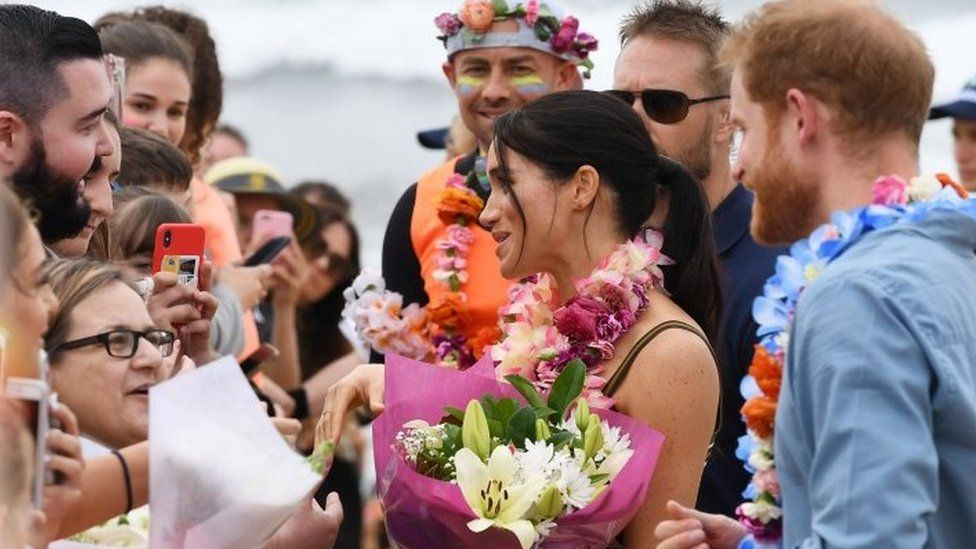 Prince Harry, the Duke of Sussex and his wife Meghan, the Duchess of Sussex receive flowers during a meet the people walk at Bondi Beach, in Sydney, Australia, 19 October 2018.