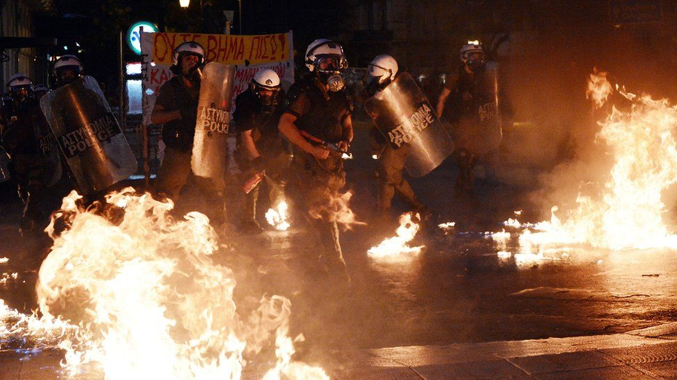 Riot police stand amid petrol bombs threw by protesters during an anti-austerity protest on July 15, 2015.