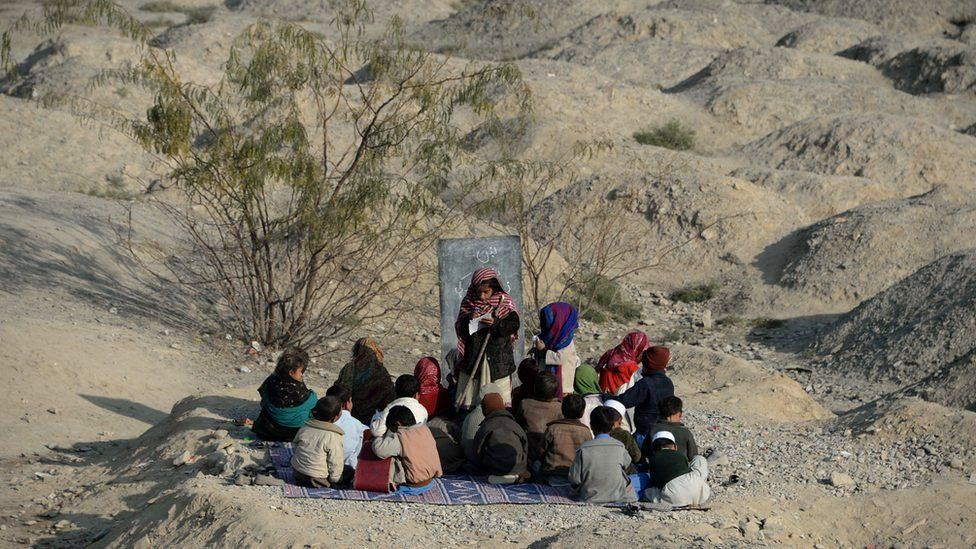 Afghan schoolchildren study at an open-air classroom in the Mohmand Dara district in eastern Nangarhar province on December 18, 2014.