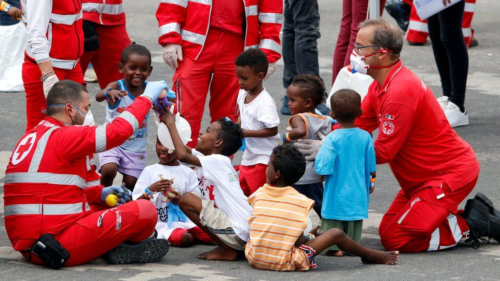 """Italian Red Cross staff play with children after they disembarked the Italian coast guard vessel """"Diciotti"""" at the port of Catania, Italy on 13 June 2018"""